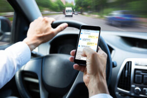 GettyImages 1021542964 300x200 Man Typing Text Message On Mobile Phone While Driving Car